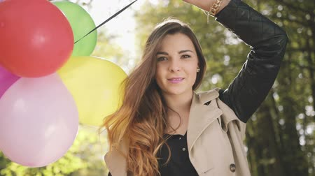 fiatal felnőttek : Cheerful brunette girl with colorful balloons smiling in autumn park.