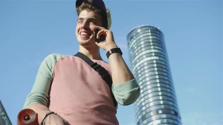 борода : Young man using a mobile phone with cityscape in the background, outdoor.