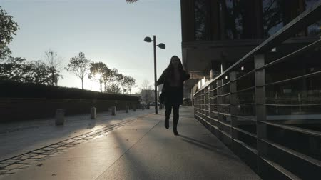 siluety : Silhouette of young girl walking joyfully in the city streets, slow motion.