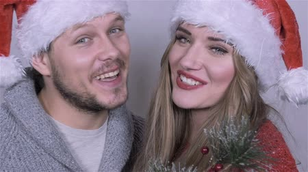 dospělý : Happy beautiful Christmas couple singing carols over white background.