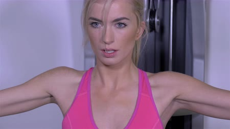 bicep : Portrait of beautiful blonde girl working out on multi gym.