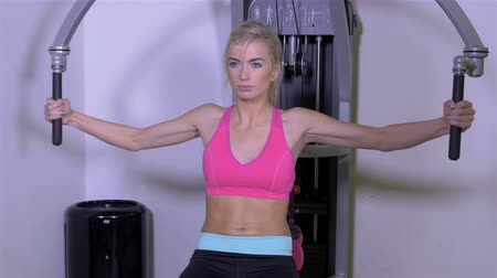 атлетика : Beautiful blonde woman at the gym exercising on a training machine. Стоковые видеозаписи