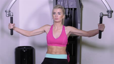 сильный : Woman at the gym doing arms exercises on a machine. Стоковые видеозаписи