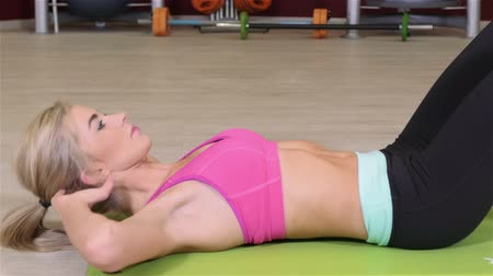 abs : Beautiful sporty woman doing crunches on the floor in a fitness center. Stock Footage