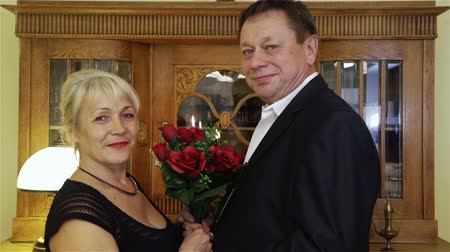 годовщина : Happy mature couple at home celebrating their anniversary. Middle-aged man giving woman bouquet of red roses. Happy senior couple with bunch of flowers at home celebrating their anniversary. Стоковые видеозаписи