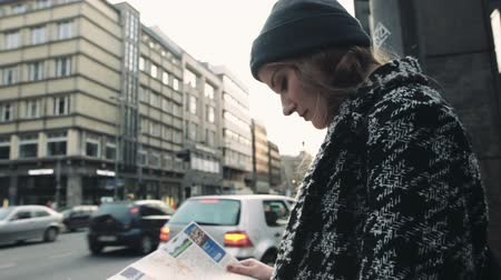 rehberlik : Young beautiful woman traveler with a map. Woman looking at city map on the street. Looking for directions.