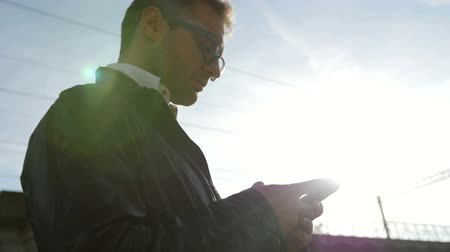 erkekler : Outdoor portrait of modern young man with mobile phone in the street. Young urban professional man using smart phone. Businessman holding mobile smartphone using app texting sms message wearing jacket.