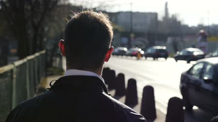 рабочих мест : Young man walking down a sidewalk, slow motion. Man walking on the street in the city, steadycam shot. Rear view.