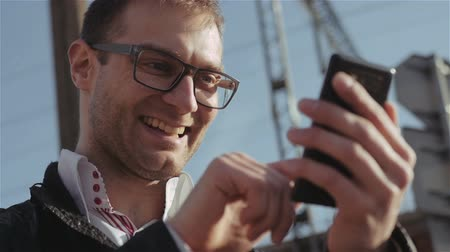 использование : Young urban businessman with smartphone using app texting sms message.