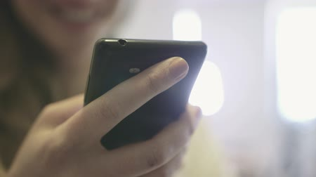 cellphone : Close up of female hands using a mobile cell phone indoors.