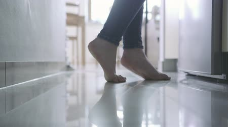 mutfak : Female legs walking without shoes in the kitchen. Woman looking at something fridge.