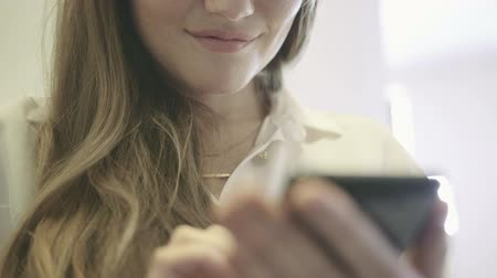 surfing the net : Young smiling woman holding a smartphone in hand and surfing in the Internet. Stock Footage