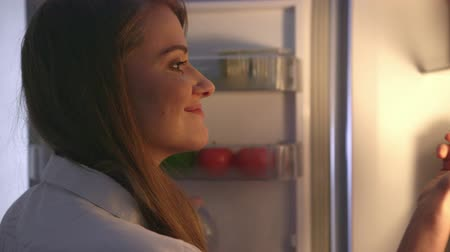 hűtőgép : Young woman taking out vegetable from the fridge. Healthy Eating Concept. Diet. Beautiful Young Woman near the Refrigerator with healthy food. Fruits and Vegetables in a Fridge. Stock mozgókép