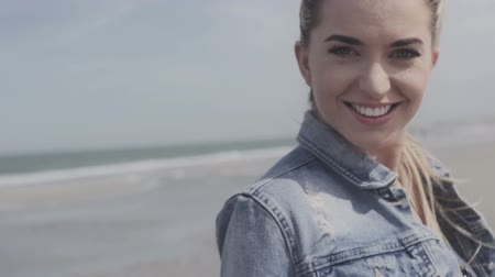 smile : Happy young woman in a denim jacket smiling to the camera on a lonely beach.