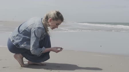 оболочка : Happy young woman in a denim jacket finding something on a lonely beach