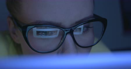 looking : Closeup shot of an attractive woman in glasses surfing the Internet at night.