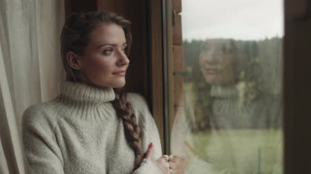 cold : Young pensive woman standing at home near a window and smiling.