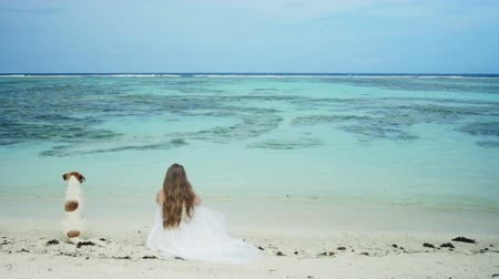 oceano : Young bride with a dog looking at beautiful ocean.