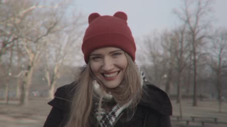 зубастая улыбка : Woman in red hat looking at camera and smiling outdoors.