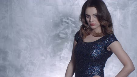 shiny : Young woman posing in an elegant sparkling black party dress against modern silver background inside a studio.
