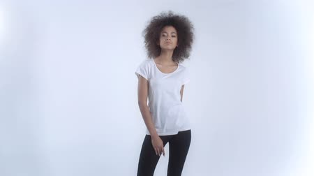 model : Young African American woman in white t-shirt posing over white background. Stock Footage