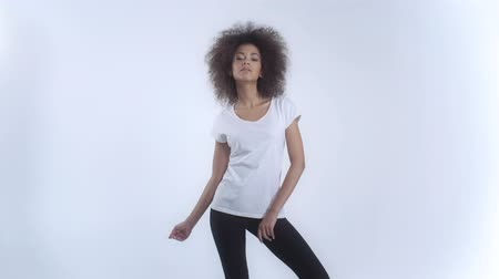 черные волосы : Young African American woman in white t-shirt posing over white background. Стоковые видеозаписи