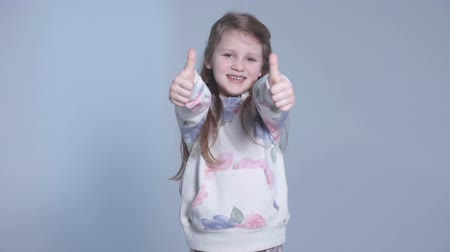 polegar : Portrait of a beautiful and confident girl showing thumbs up, studio.