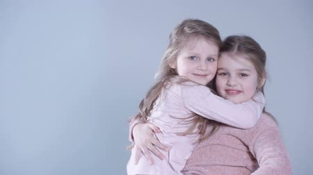 két : Two lovely little girls playing in the studio. Younger sister jumping straight to an olders arms in slow motion.