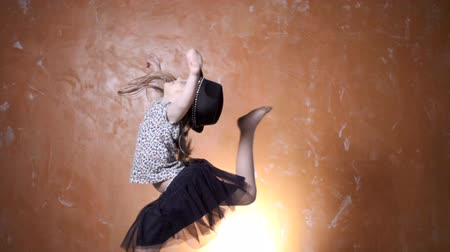 zeď : Pretty girl in a beautiful dress and a hat jumping in the studio. Cute girl jumping over orange modern background.