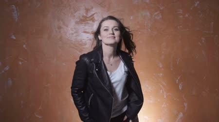 couro : Beautiful trendy woman dancing over orange background. Beautiful brunette woman wearing a leather jacket posing in studio, slow motion.