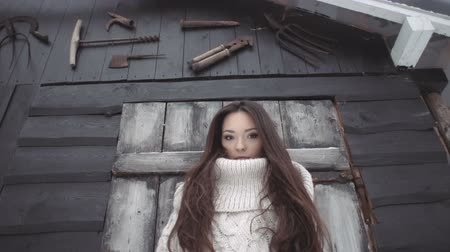 pulóver : Beautiful young woman wearing knitted sweater posing by the shed with tools. Smiling young woman in bright sweater in winter scenery, snowy background. Fall and winter fashion concept. Stock mozgókép