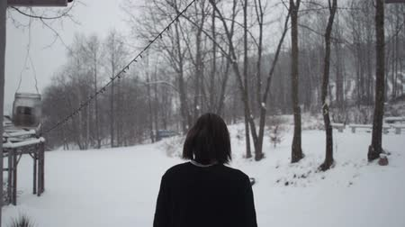 walk behind : Young man in black sweater walking to a winter forest, rear view. Winter scene of man walking near an old wooden house. Snowy background. Slow motion.