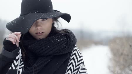 модный : Stylish fashion portrait. Outdoor winter portrait of young brunette wearing a hat over snowy background. Стоковые видеозаписи