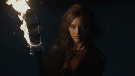 mystik : Portrait of a young mystic woman in the dark forest holding a torch.