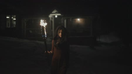 mystik : Portrait of a young mystic woman in the dark holding a torch.