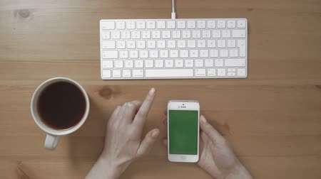 teclado : Woman checking on phone with green screen. White keyboard on a wooden table. Women hands holding the phone with isolated screen and cup of coffee in the office. Vídeos