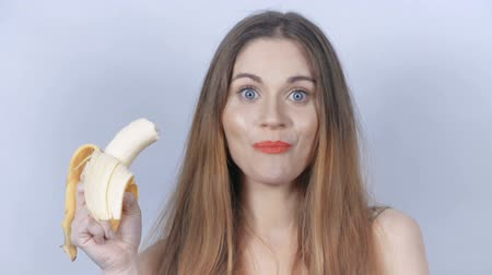 голодный : Portrait of attractive caucasian smiling woman isolated on gray background eating a banana. Long haired woman with fresh fruit.