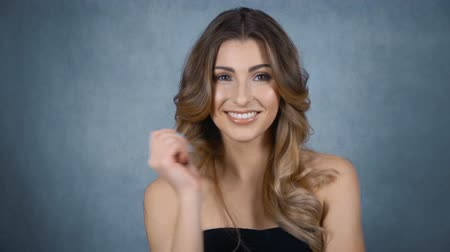 cabelos grisalhos : Cute smiling woman on gray background. Beautiful face of young adult woman with clean fresh skin - studio portrait. Slow motion. Vídeos