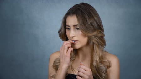 morder : Beautiful young woman biting her nails in the studio. Young stressed woman biting her nails over gray background. Stock Footage