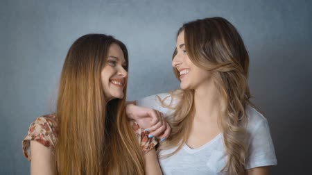 зубастая улыбка : Portrait of two attractive caucasian smiling women isolated on gray background. Toothy smile long hair head and shoulders looking at camera models.