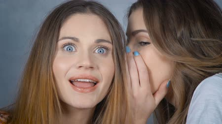 kulaklar : Portrait of a young woman telling her friend a secret in the studio. Friendship, people and communication concept - happy young women gossiping and whispering to ear over gray background. Stok Video