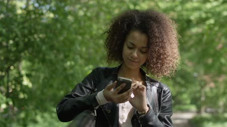 couro : Portrait of relaxed young lady in a summer park reading a text message on her mobile phone.