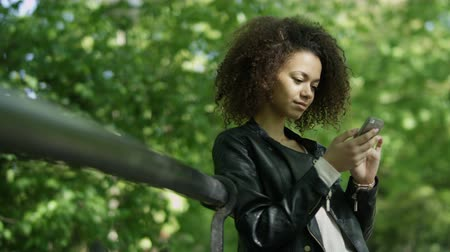 telefone celular : Portrait of relaxed young lady in a summer park reading a text message on her mobile phone.