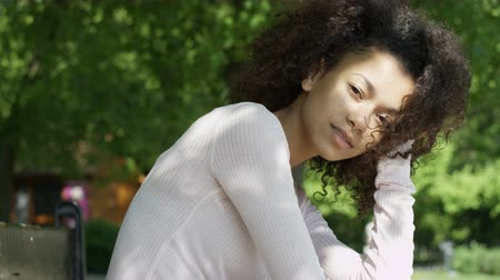 kıvırcık saçlar : Young beautiful mixed race woman with curly afro hair smiling happily in a green park.