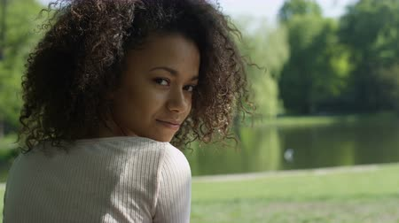 kıvırcık : Young beautiful mixed race woman with curly afro hair smiling to the camera in a green park.