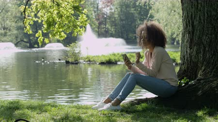 kıvırcık : Beautiful young girl with dark curly hair using her cell phone, outdoor.
