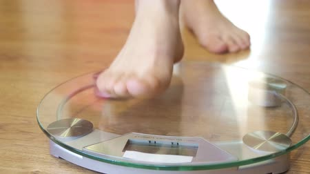 com escamas : Female bare foot touching and pushing scales surface standing on the floor Stock Footage