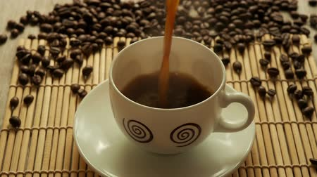 coffee grounds : Black coffee in a white cup on a mat from a bamboo background coffee beans close Stock Footage