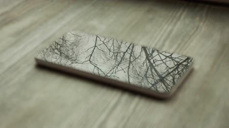 interactive table : Movement of the trees are reflected in the screen of your smartphone on a background of a wooden table Stock Footage