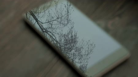 interactive table : Movement of the trees are reflected in the screen of your smartphone on a background of a wooden table closeup